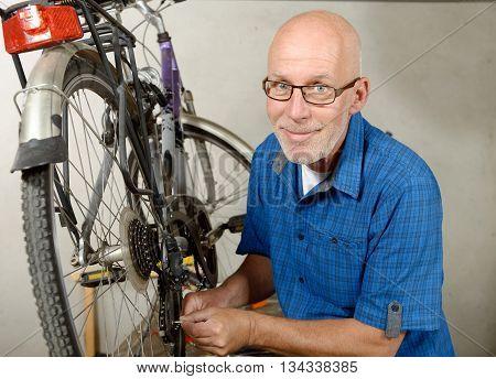 man repairing bike gear in his workshop.