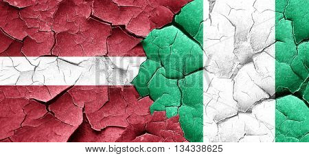 Latvia flag with Nigeria flag on a grunge cracked wall