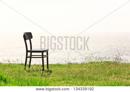 Black chair on the hill by the sea