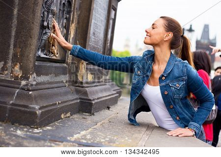 a beautiful young woman touching the bronze plaque on charles bridge for good luck