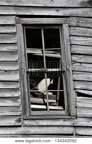 Dilapidated abandoned wooden home with a broken window