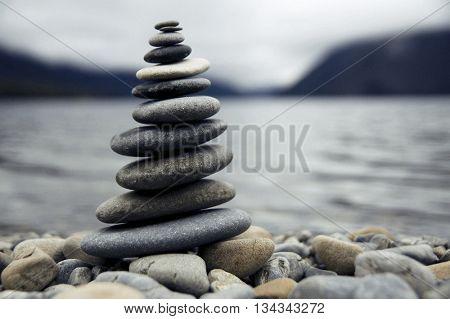 Zen balancing pebbles next to a misty lake.