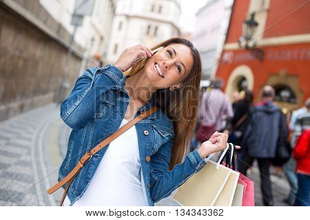 young woman chatting to her friends on the phone while out shopping
