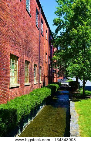 Creek alongside an older brick warehouse building with lush green landscaping