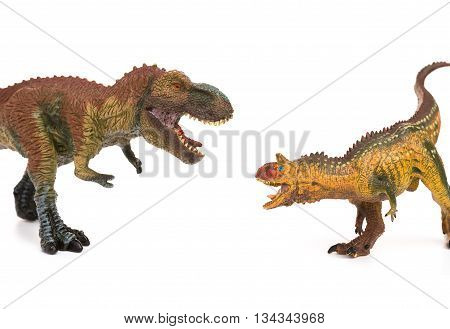 tyrannosaurus and carnotaurus toys on white background