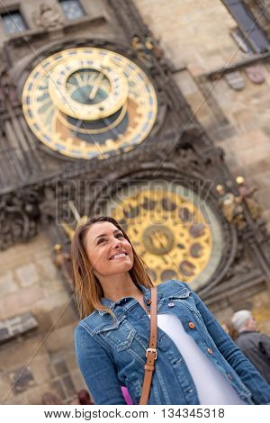 young woman in prague with the astronomical clock behind her