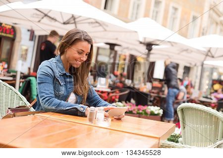 young woman watching a film on her phone at a restaurant