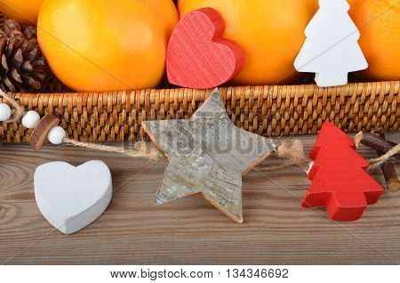 Orange in wickered tray on wooden background with Christmas decor