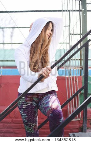 Portrait of an attractive young woman with sport clothes at stairs.