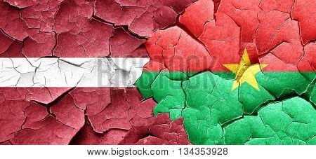 Latvia flag with Burkina Faso flag on a grunge cracked wall