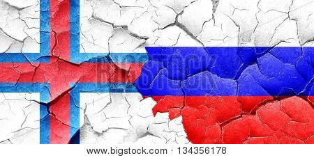 faroe islands flag with Russia flag on a grunge cracked wall