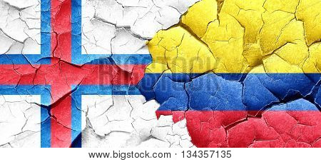 faroe islands flag with Colombia flag on a grunge cracked wall