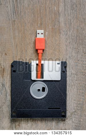 Used floppy diskettes with orange USB cable Plug on wooden backgrounddesign for technology concept