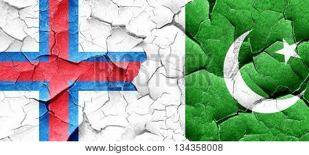 faroe islands flag with Pakistan flag on a grunge cracked wall