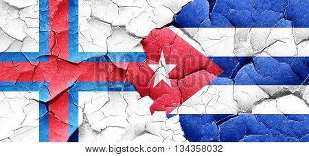 faroe islands flag with cuba flag on a grunge cracked wall