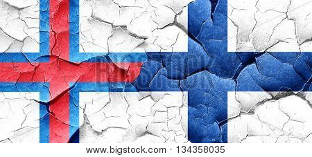 faroe islands flag with Finland flag on a grunge cracked wall