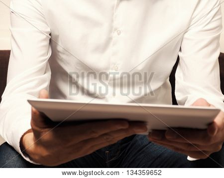 Businessman with a tablet computer reading an ebook selective focus on man