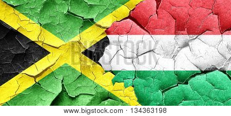 Jamaica flag with Hungary flag on a grunge cracked wall