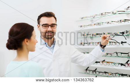 health care, people, eyesight and vision concept - optician showing glasses to woman at optics store
