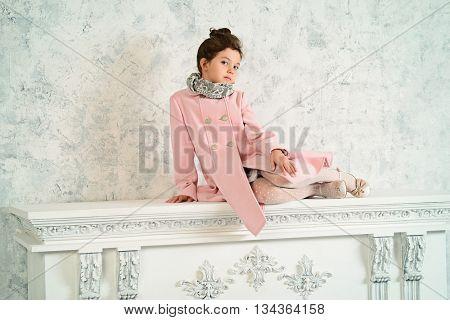 Elegant eight-year girl in the vintage interior. Kid's fashion.