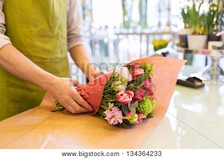 people, shopping, sale, floristry and consumerism concept - close up of florist man wrapping flowers