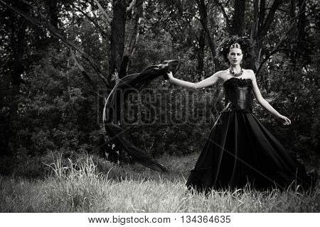 Black-and-white portrait of a magnificent brunette woman wearing long black dress walking in a mystic forest. The old times, the Gothic style. Fashion.