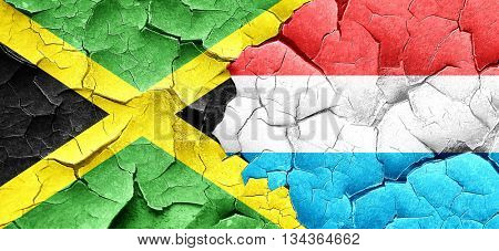 Jamaica flag with Luxembourg flag on a grunge cracked wall