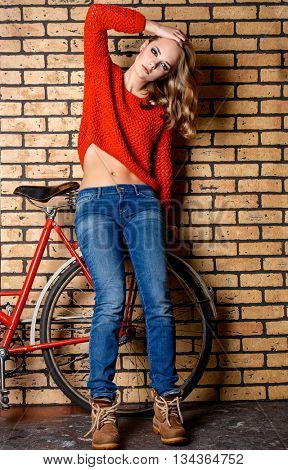 Modern girl teenager posing with her bicycle by a brick wall. Teen generation. Youth fashion style.