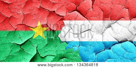 Burkina Faso flag with Luxembourg flag on a grunge cracked wall
