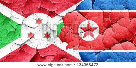 Burundi flag with North Korea flag on a grunge cracked wall