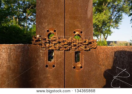 A door is chained and rusted even though one can pass thru the back