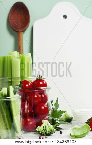 Assorted fresh vegetables with dip and White ceramic serving board with space for your text