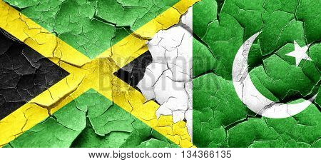 Jamaica flag with Pakistan flag on a grunge cracked wall