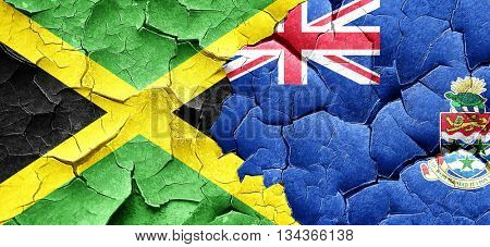 Jamaica flag with Cayman islands flag on a grunge cracked wall