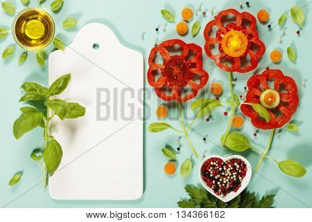 Cute flowers made of fresh organic vegetables on blue background - Cooking, Gardening, Raw Food, Vegetarian or Clean Eating concept