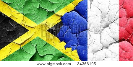 Jamaica flag with France flag on a grunge cracked wall