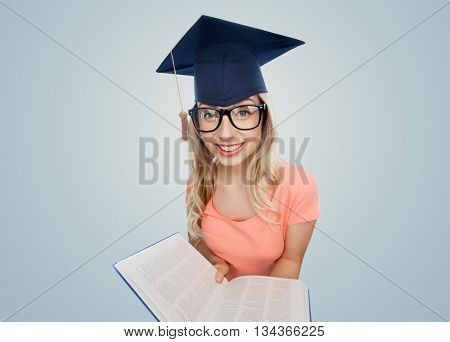 people, education, knowledge and graduation concept - smiling young student woman in mortarboard and eyeglasses with encyclopedia book over gray background