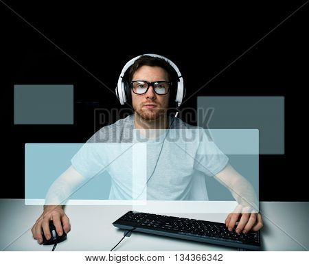 technology, gaming, let's play and people concept - young man or hacker in headset and eyeglasses with pc computer playing game and streaming playthrough or walkthrough video with virtual screens