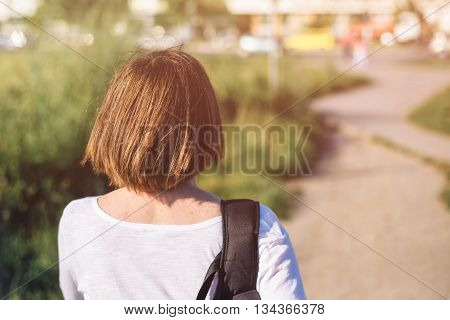 Casual ordinary young adult woman in everyday activity walking on city streets from behind selective focus