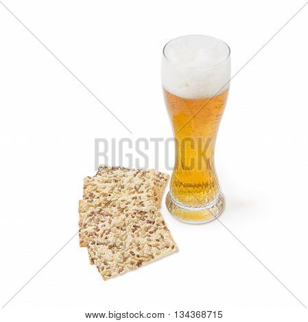 Beer glass with lager beer and savory biscuits with sesame seeds flax seeds and sunflower on a light background