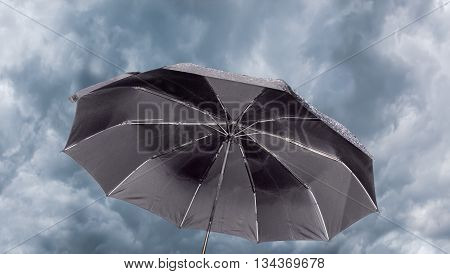 Open male black folding umbrella against the background of sky with thunder clouds