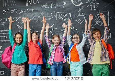 Group of happy schoolchildren standing in front of the blackboard with hands up