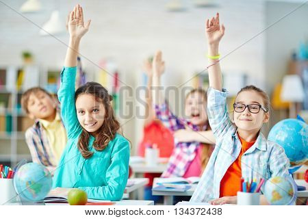 Clever pupils raising hands during lesson