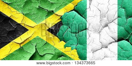 Jamaica flag with Nigeria flag on a grunge cracked wall