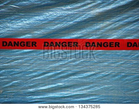 Red Danger Tape Over a Blue Wall Background