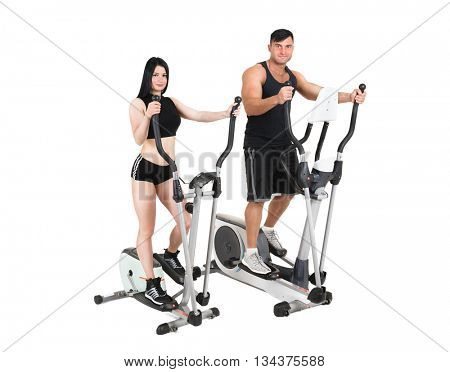 young woman and man doing exercises on elliptical cross trainer