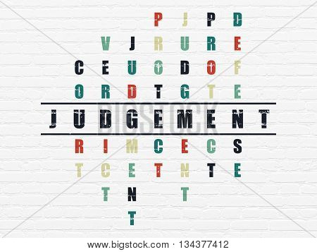 Law concept: Painted black word Judgement in solving Crossword Puzzle