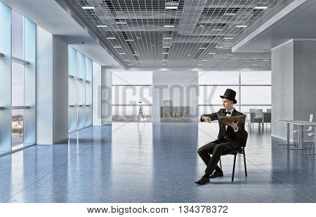 Businessman in cylinder reading book