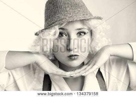 Beautiful woman in hat, business style. Blonde girl holding her hands near to the face, attractive woman with beautiful eyes. Handsome woman with sensual lips in gangster style.