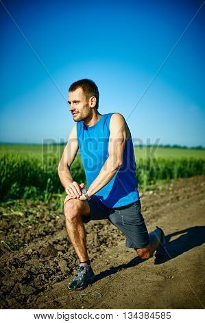 man runner athlete warming up before jogging along a green field in the early morning. man lunged forward on one knee. man fitness sunset jogging workout wellness concept.